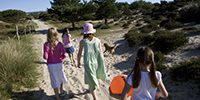 Children walking through the nature reserve to the dunes and beach at Studland, Dorset